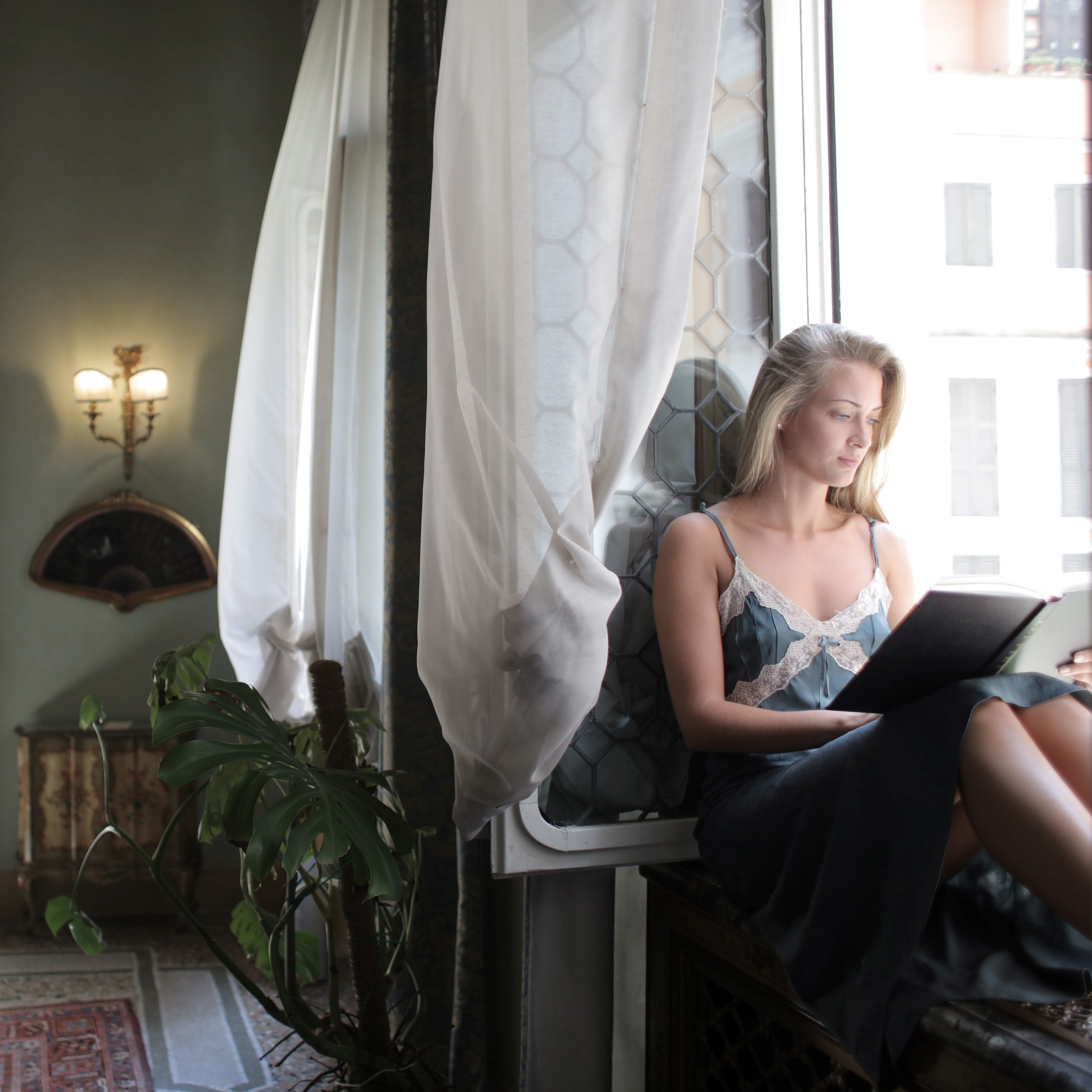 Canva - Woman Wearing Blue Dress While Reading a Book