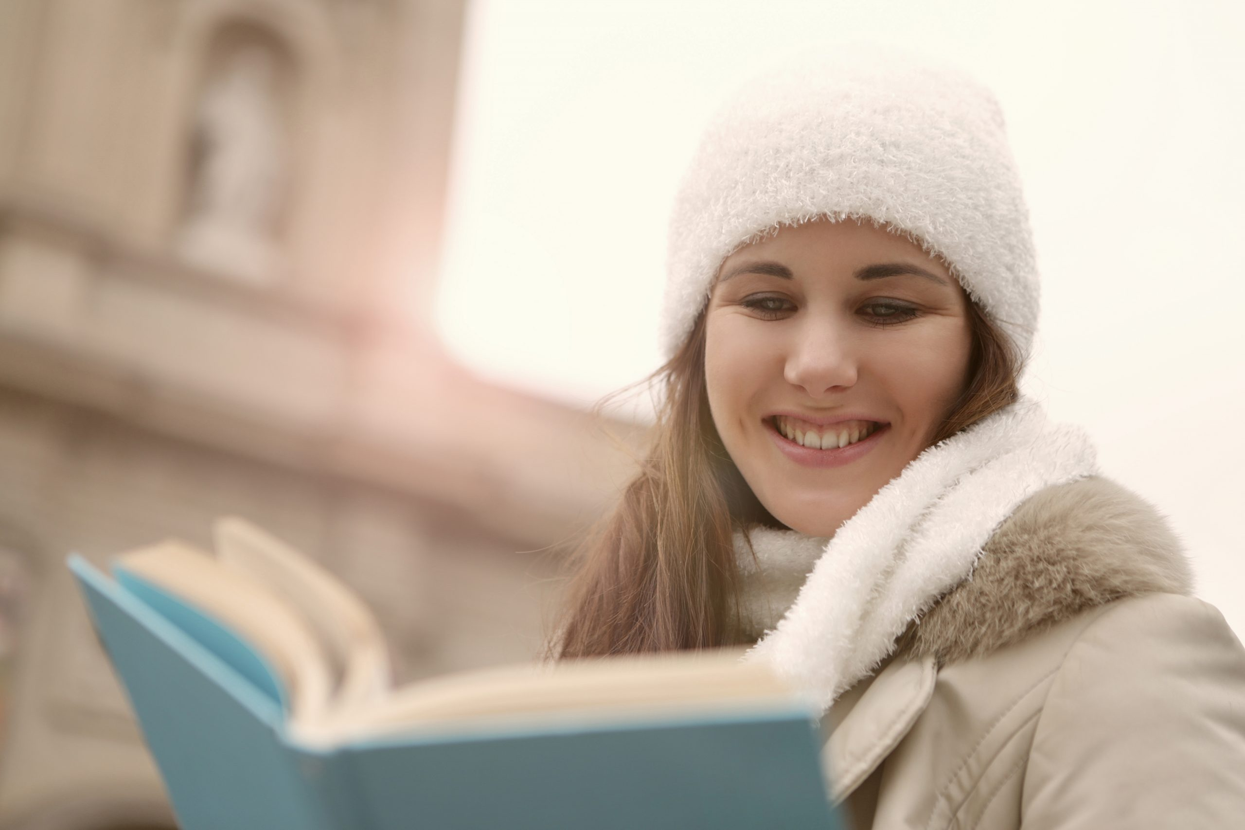 Canva - A Happy Woman in White Knitted Beanie Reading a Book